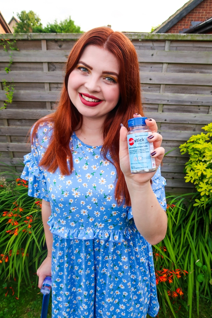 a midshot of Jenni a white woman with straight auburn hair is wearing a light blue dress with a small daisy pattern she is holding a bottle of vitassium a clear bottle with a dark blue top and pale blue label. she is using a blue walking stick and standing in a garden surrounded by plants.